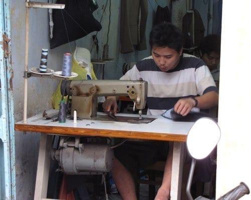 man sewing a garment in vietnam