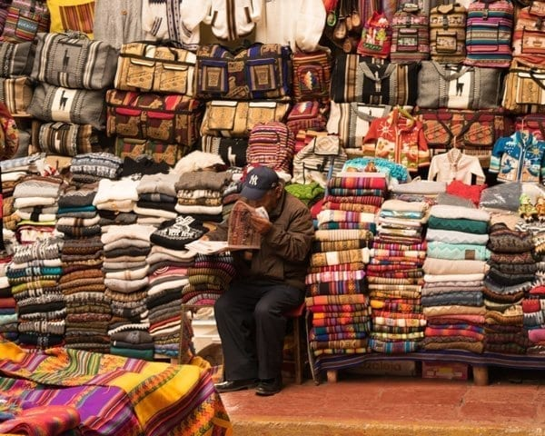 Man in Yankees hat selling knits from an open market in central Cusco, Peru.