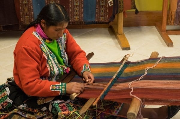 woman practicing traditional incan weaving at center for traditional textiles